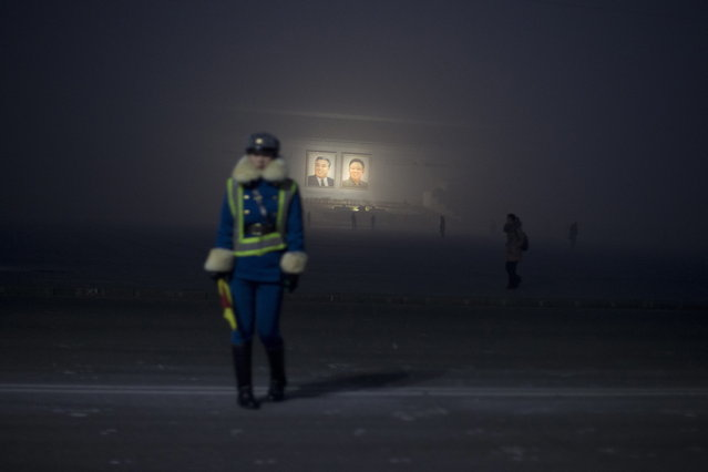 A North Korean traffic coordinator stands on a roadside near portraits of the late leaders Kim Il Sung, left, and Kim Jong Il during a foggy morning on Kim Il Sung Square in Pyongyang, North Korea, Monday, December  17, 2012. (Photo by Ng Han Guan/AP Photo)