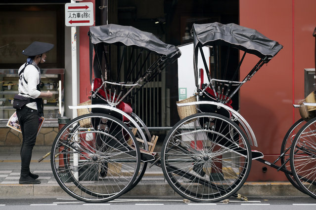 A rickshaw puller waits for tourists near Sensoji Temple in Asakusa district Thursday, October 22, 2020, in Tokyo. (Photo by Eugene Hoshiko/AP Photo)