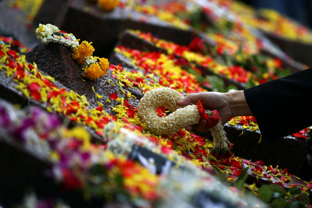A woman lays a garland on a memorial during the 40th anniversary of a campus massacre by state forces in the military-ruled country at Thammasart University in Bangkok, Thailand. October 6, 2016. (Photo by Athit Perawongmetha/Reuters)