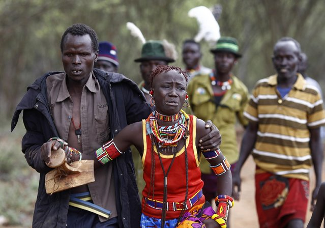 A man holds onto a girl as he brings her back to her family home after she tried to escape when she realised she is to be married, about 80 km (50 miles) from the town of Marigat in Baringo County December 7, 2014. (Photo by Siegfried Modola/Reuters)