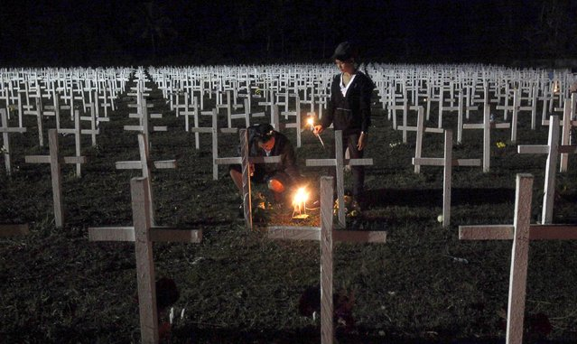 Residents light candles at the graves of their loved ones at a mass grave for Typhoon Haiyan victims on All Saints Day in Tacloban city in central Philippines November 1, 2015. (Photo by Lorgina Minguito/Reuters)
