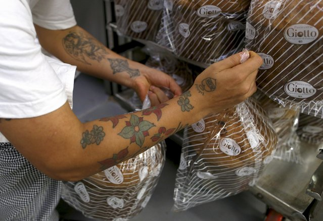 Prison baker places some panettone cakes on rack at the Pasticceria Giotto in Padua's Due Palazzi prison December 2, 2014. (Photo by Alessandro Bianchi/Reuters)