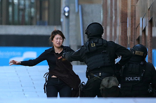 A hostage runs to armed tactical response police officers for safety after she escaped from a cafe under siege at Martin Place in the central business district of Sydney, Australia, Monday, December 15, 2014. (Photo by Rob Griffith/AP Photo)
