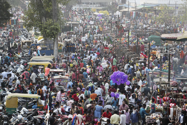 Indians throng a market for shopping ahead of Hindu festival Diwali in Ahmedabad, India, Thursday, November 12, 2020. India's tally of coronavirus cases is currently the second largest in the world behind the United States. The government warns that the situation can worsen due to people crowding markets for festival shopping. (Photo by Ajit Solanki/AP Photo)