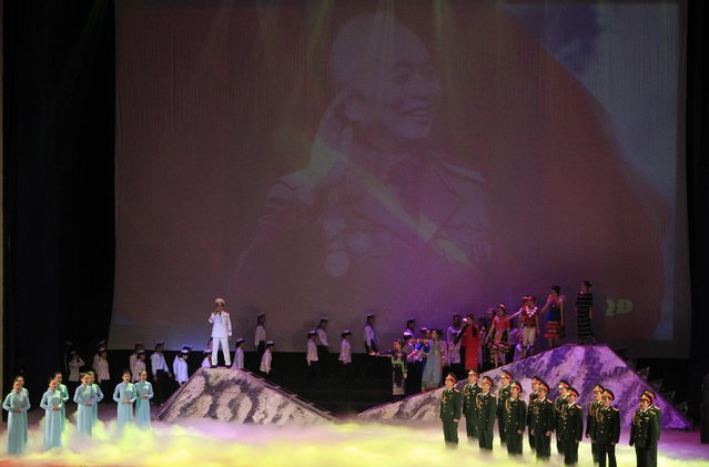 People perform in front of a screen showing an image of General Vo Nguyen Giap during celebrations to commemorate the 70th anniversary of the establishment of the Vietnam People's Army at the National Convention Center in Hanoi December 20, 2014. (Photo by Reuters/Kham)