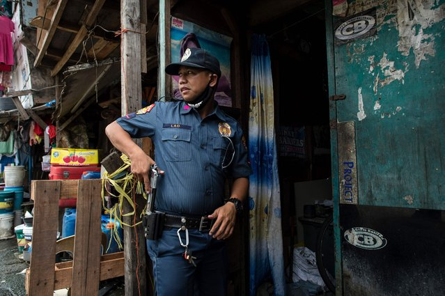 """A police officers draws his gun as he is about to enter a house during an """"Oplan Tokhang"""" or house-to-house campaign on illegal drugs at an informal settlers community in Manila on October 6, 2016. Philippine President Rodrigo Duterte told all his critics to """"go to hell"""" on October 6, as he renewed his threats to kill, after a poll showed Filipinos overwhelmingly endorsed his deadly war on crime. (Photo by Noel Celis/AFP Photo)"""