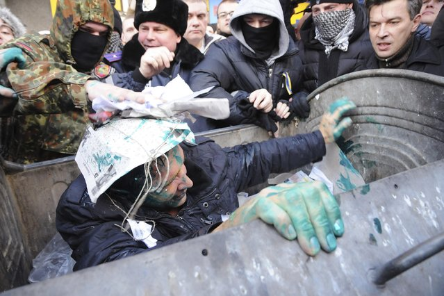 Vladimir Skorobagach, deputy of the Kharliv city council, reacts after being thrown by activists into a garbage container during a protest for the resignation of the Kharkiv's mayor Gennady Kernes outside the city council in Kharkiv, December 24, 2014. (Photo by Reuters/Stringer)