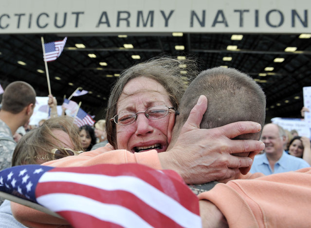 In this August 25, 2010 file photo, Janet Allegra, of Ellington, hugs her son Spc. John Allegra IV at the Army aviation support facility in Windsor Locks, Conn.  About 110 soldiers of the 250th Engineer Co. Connecticut National Guard who were deployed to Iraq last winter have returned home. (Photo by Jessica Hill/AP Photo)