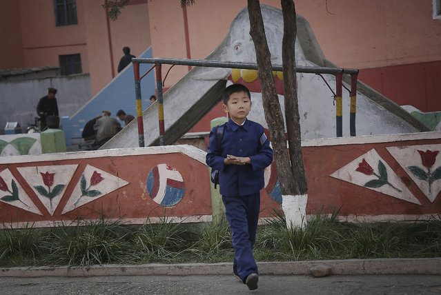 A North Korean boy in his school uniform walks past a playground in a residential area on Saturday, October 15, 2016, in Pyongyang, North Korea. (Photo by Wong Maye-E/AP Photo)