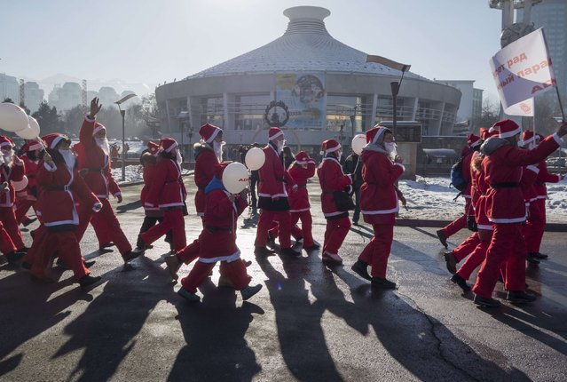 Revelers dressed as Father Frost, the equivalent of Santa Claus, walk past a building that holds circus performances during a parade in Almaty December 28, 2014. (Photo by Shamil Zhumatov/Reuters)
