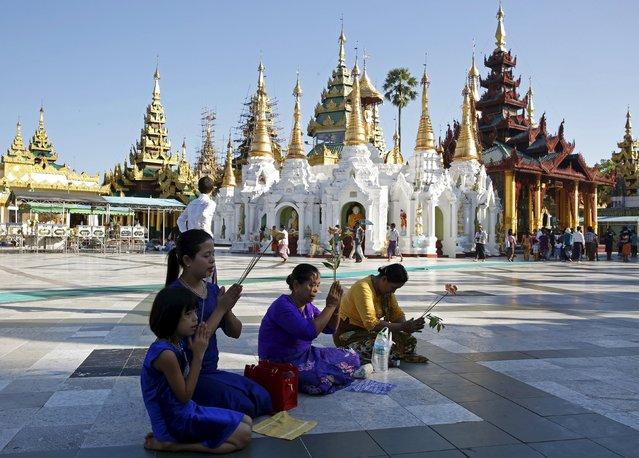 A family prays together at Shwedagon Pagoda in Yangon, Myanmar, November 13, 2015. (Photo by Olivia Harris/Reuters)
