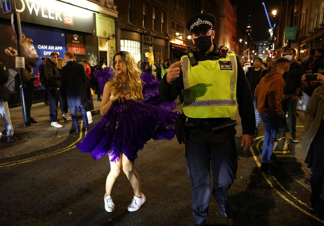 A police officer patrols as people party on a street as pubs shut for the night due to tier 3 restrictions in Soho, as the spread of the coronavirus disease (COVID-19) continues in London, Britain, December 15, 2020. (Photo by Henry Nicholls/Reuters)