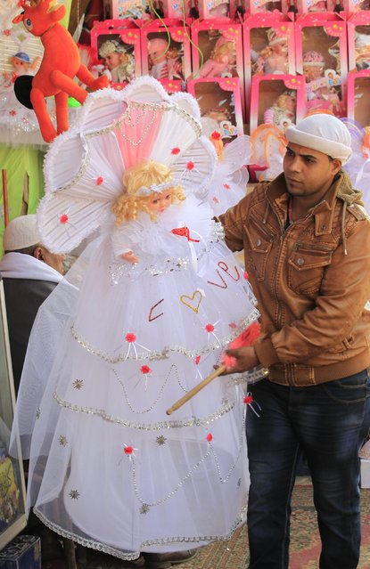 "A man sells traditional doll toys for children to celebrate the birthday of prophet Muhammad, also known as ""mawlid al nabi"", which will fall next week, in a makeshift tent in Cairo, December 30, 2014. (Photo by Mohamed Abd El Ghany/Reuters)"