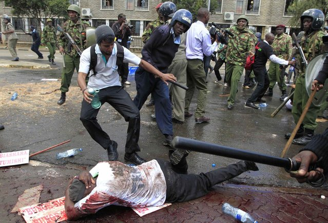 A protestor tries to help another protestor from being attacked by riot policemen as they participate in a demonstration against lawmakers' salary demands outside the parliament buildings in the capital Nairobi, May 14, 2013. (Photo by Thomas Mukoya/Reuters)