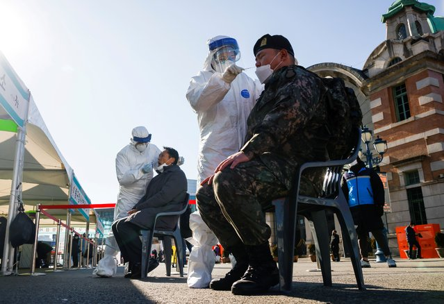A South Korean soldier undergoes a coronavirus disease (COVID-19) test at a coronavirus testing site which is temporarily set up at a railway station in Seoul, South Korea, December 15, 2020. (Photo by Kim Hong-Ji/Reuters)