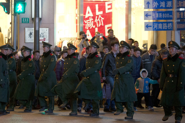 Chinese paramilitary policemen form human chains to guide pedestrians crossing a major intersection near the site of a deadly stampede in Shanghai, China, Thursday, Jan. 1, 2015January 1, 2015.  (Photo by Ng Han Guan/AP Photo)