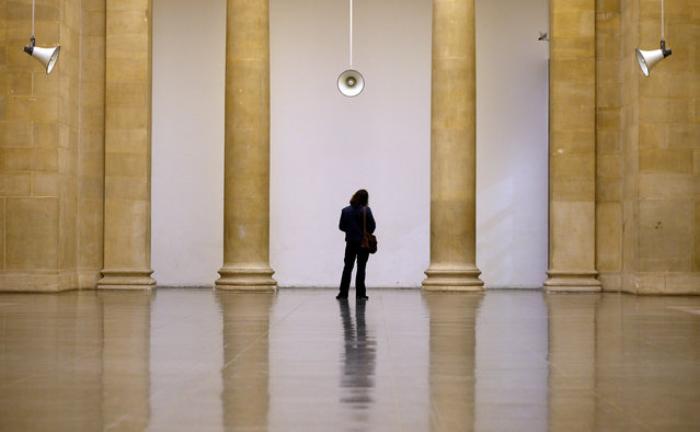 A visitor listens to sounds played through speakers at an exhibition entitled 'War Damaged Musical Instruments' at the Tate Britain museum in London, Friday, November 20, 2015. The exhibition which marks the centenary of the First World War features recordings of damaged British and German musical instruments playing isolated tones from 'The Last Post'. (Photo by Kirsty Wigglesworth/AP Photo)