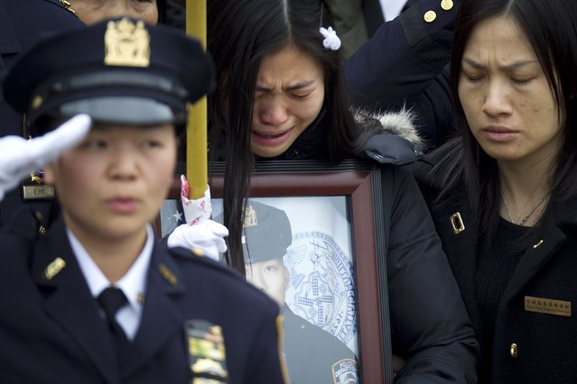 Widow Pei Xia Chen reacts while clutching a photo of slain New York Police Department officer Wenjian Liu as his casket departs his funeral in the Brooklyn borough of New York January 4, 2015. New York Mayor Bill de Blasio appealed for reconciliation on Sunday in his eulogy for the second of two police officers murdered last month, two deaths that led to accusations the mayor had contributed to an anti-police climate. (Photo by Carlo Allegri/Reuters)