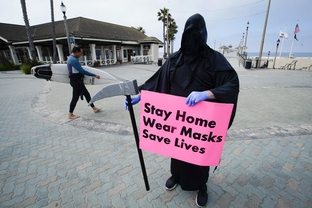 Spencer Kelly, dressed as the grim reaper, demonstrates in favor of the stay-at-home order during the coronavirus pandemic at the pier Friday, May 8, 2020, in Huntington Beach, Calif. (Photo by Chris Carlson/AP Photo)
