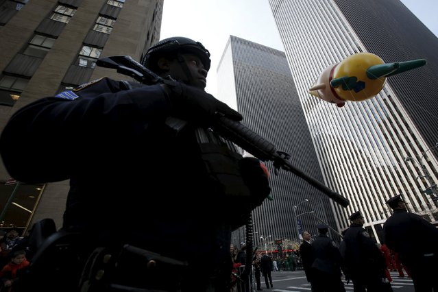 Members of the New York Police Department's Emergency Service Unit watches as balloons pass during the 89th Macy's Thanksgiving Day Parade in the Manhattan borough of New York, November 26, 2015. (Photo by Andrew Kelly/Reuters)