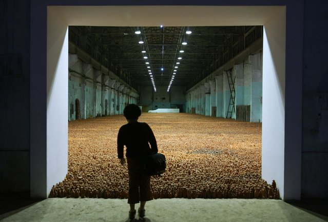 "A Chinese visitor views a massive sculptural installation filling a factory warehouse at an exhibition by British artist Antony Gormley called ""Asian Field"" in Shanghai October 7, 2003. ""Asian Field"" is comprised of 192,000 clay figures, made under the guidance of Gormley, by over 300 people of all ages in China's Guangdong province using more than 100 tons of clay. (Photo by Claro Cortes IV/Reuters)"