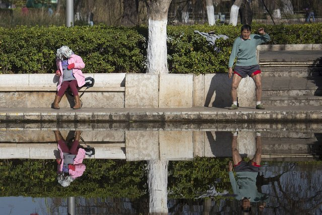 A man exercises as a woman rests at Cuihu Park  in Kunming, Yunnan province January 22, 2015. (Photo by Wong Campion/Reuters)