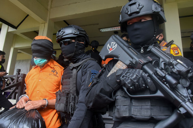 Police escort one of the group of 19 terror suspects that are being transferred to Jakarta from Makassar, at the Sultan Hasanuddin airport in Makassar on February 4, 2021. (Photo by Indra Abriyanto/AFP Photo)