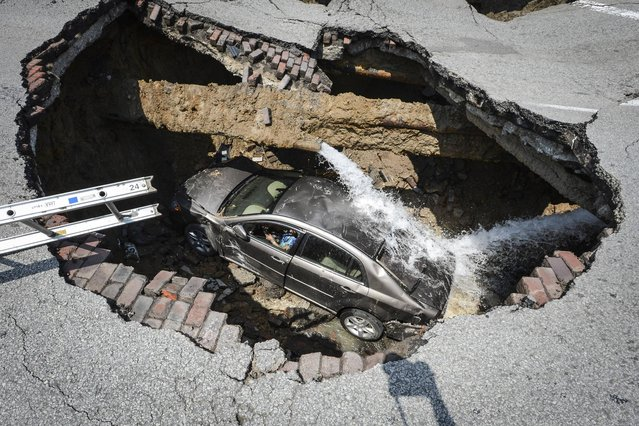 This photo provided by the Toledo, Ohio Fire and Rescue Department shows a car at the bottom of a sinkhole caused by a broken water line in Toledo, Ohio on Wednesday, July 3, 2013. Police say the driver, 60-year-old Pamela Knox of Toledo, was shaken up and didn't appear hurt but was taken to a hospital as a precaution. (Photo by Lt. Matthew Hertzfeld)/AP Photo/Toledo, Ohio Fire and Rescue Department)