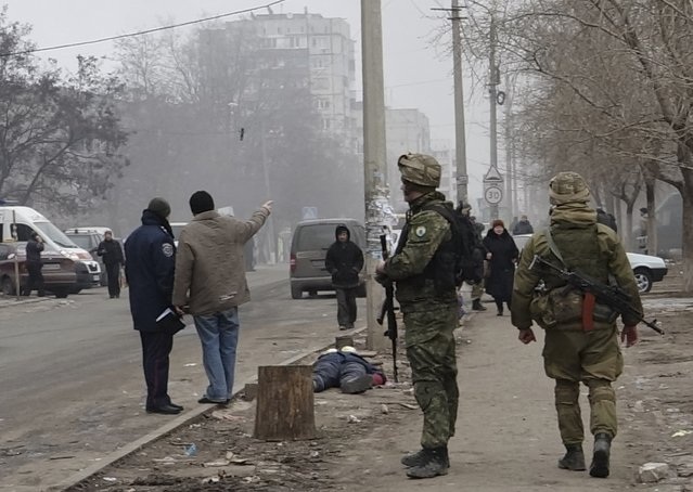 Ukrainian servicemen guard a street, near the body of a victim killed by a recent shelling of a residential sector, in Mariupol, eastern Ukraine, January 24, 2015. At least 20 people were killed by shelling in the east Ukrainian port city of Mariupol on Saturday, regional police said, as a rebel leader said separatists were launching an offensive on the city, the news agency RIA reported. (Photo by Nikolai Ryabchenko/Reuters)