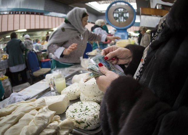 A customer holds tenge banknotes while visiting the dairy department of the Green Bazaar in Almaty January 24, 2015. (Photo by Shamil Zhumatov/Reuters)