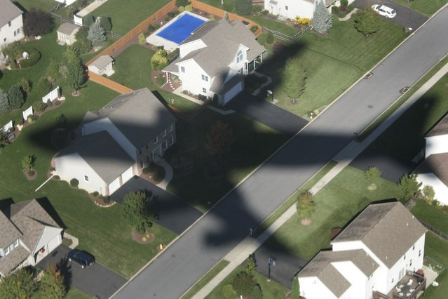 Air Force One casts its shadow over homes as it comes in to land in Allentown, Pennsylania with U.S. President George W. Bush aboard in this October 1, 2004 file photo. (Photo by Jason Reed/Reuters)