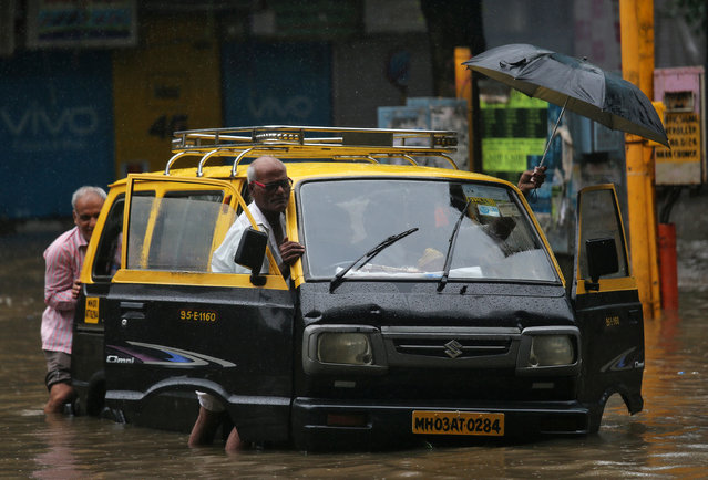 People push a taxi through a waterlogged street after heavy rains in Mumbai, July 8, 2018. (Photo by Francis Mascarenhas/Reuters)