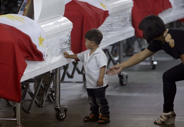 Christine Kiangan, widow of Noble Kiangan, one of the 44 members of the elite police commandos killed last Sunday during the Philippines' biggest single-day combat loss in recent years, reaches out to her son as he touches a commando's flag-draped coffin at Camp Bagong Diwa, Taguig city, south of Manila, Philippines, on Friday, January 30, 2015. (Photo by Bullit Marquez/AP Photo)