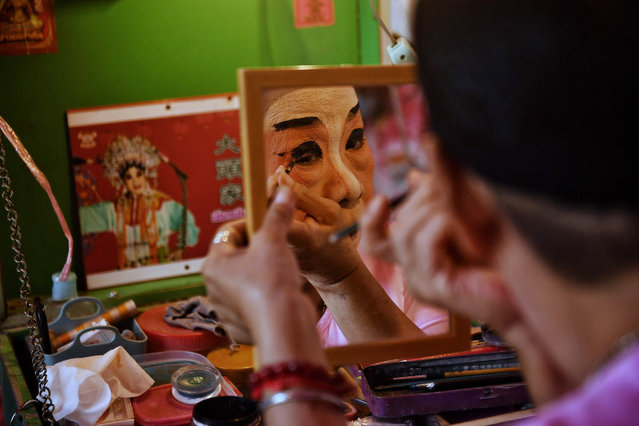 A traditional Chinese Opera performer from the Sai Yong Hong troupe applies eye makeup backstage before a performance on the first day of the Lunar New Year in Bangkok on February 12, 2021. (Photo by Lillian Suwanrumpha/AFP Photo)