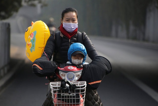 A woman and her son wearing masks ride an electric bicycle on a hazy day in Beijing, China, November 4, 2016. (Photo by Jason Lee/Reuters)
