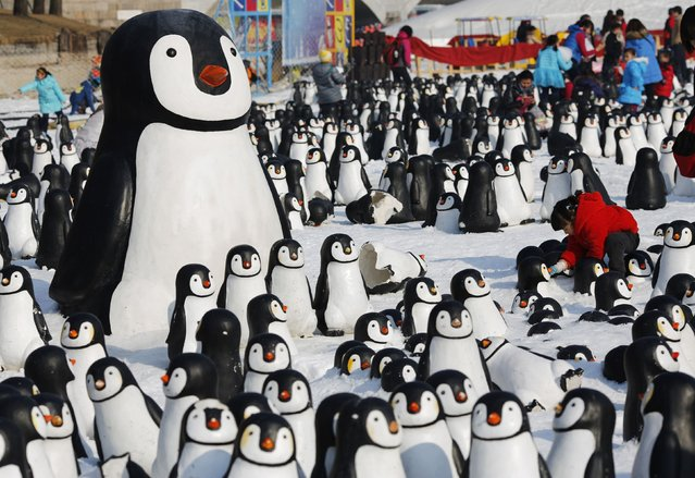 A girl plays with snow inside a display of plastic penguins during the Ice and snow carnival at Taoranting park in Beijing February 9, 2015. (Photo by Kim Kyung-Hoon/Reuters)
