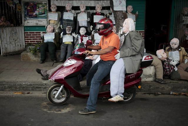 A man carries on his motorcycle a handmade puppet in Managua, Nicaragua December 30, 2015. (Photo by Oswaldo Rivas/Reuters)