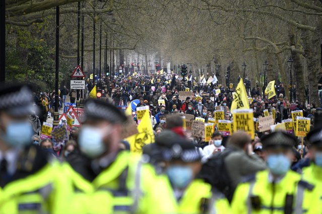 """Demonstrators hold banners and flags during a """"Kill the Bill"""" protest in London, Saturday, April 3, 2021. The demonstration is against the contentious Police, Crime, Sentencing and Courts Bill, which is currently going through Parliament and would give police stronger powers to restrict protests. (Photo by Alberto Pezzali/AP Photo)"""