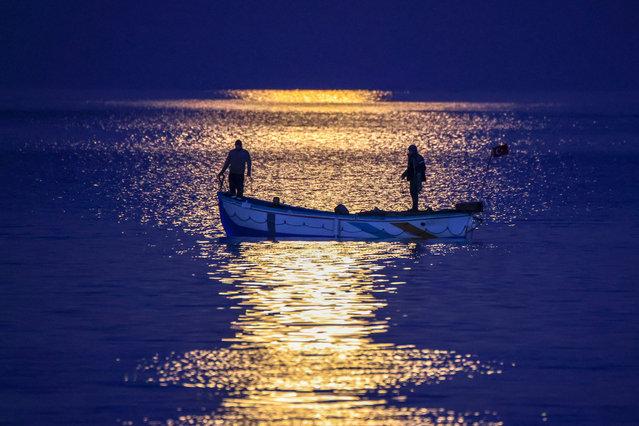 Fishermen sail in the moonlight in the Lake Van on February 27, 2021, in Van, Turkey. (Photo by Özkan Bilgin/Anadolu Agency via Getty Images)