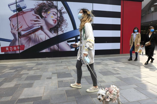 A woman walks her dog in a retail district in Beijing on Thursday, April 15, 2021. (Photo by Ng Han Guan/AP Photo)