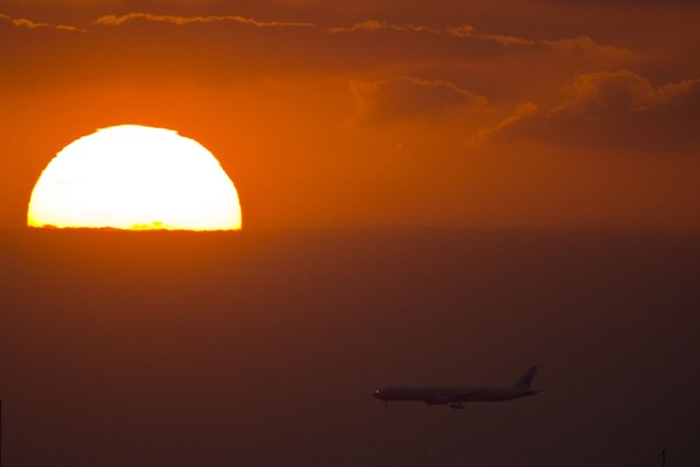 A passenger jet flies past the setting sun in Shanghai September 17, 2013. (Photo by Reuters)