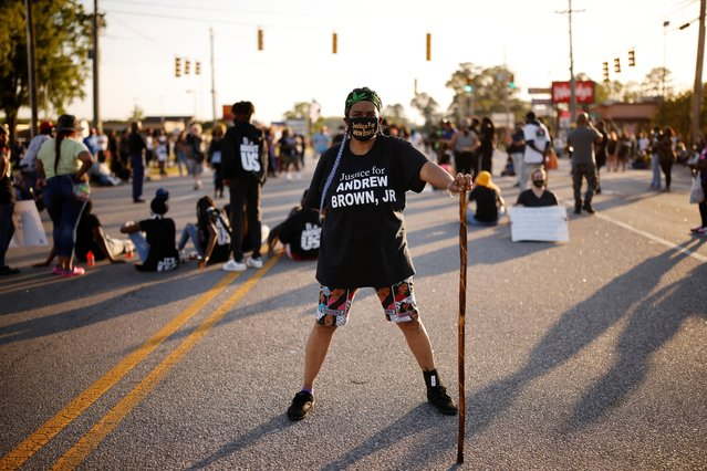 A protester stands guard as demonstrators occupy a busy intersection a week after Andrew Brown Jr. was killed by sheriff's deputies in Elizabeth City, North Carolina, U.S. April 28, 2021. (Photo by Jonathan Drake/Reuters)