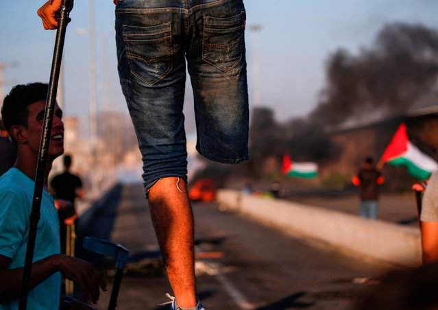 A Palestinian amputee protester stands with a crutch on a concrete barricade while smoke plumes from burning tires billow in the background, during clashes with Israeli forces following a demonstration at the Erez border crossing with Israel in the northern Gaza Strip on September 26, 2018. (Photo by Said Khatib/AFP Photo)