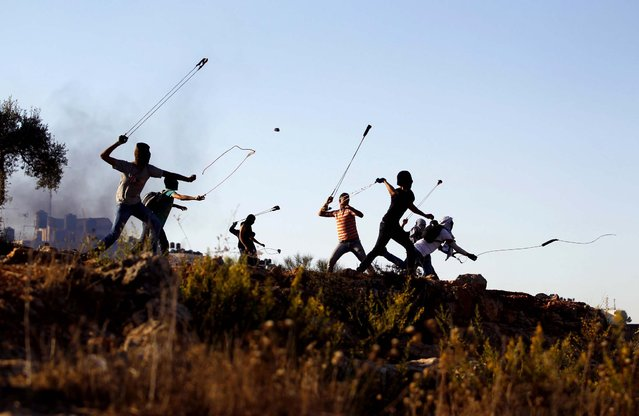 Palestinian protesters hurl rocks at Israeli soldiers during clashes in Betunia, near the West Bank city of Ramallah, on Oktober 11, 2013. (Photo by Mohamad Torokman/Reuters)