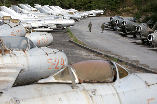 Albanian Air Force members walk near dozens of MiG-s jet fighters in Kucova Air Base in Kucova, Albania on October 3, 2018. Long the graveyard of its once mighty air force, Albania's base at Kucova is set to become a NATO station - to the delight of its former airmen longing to hear the engines roar again. (Photo by Florion Goga/Reuters)