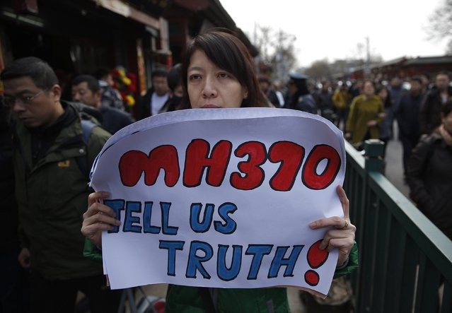 Catherine Gang, whose husband Li Zhi was onboard the missing Malaysia Airlines flight MH370, holds a banner as she walks outside Yonghegong Lama Temple after a gathering of family members of the missing passengers in Beijing March 8, 2015. Prime Minister Najib Razak said on Sunday Malaysia remains committed to the search for the missing MH370 jetliner a year after it vanished without trace and he is hopeful it will be found.