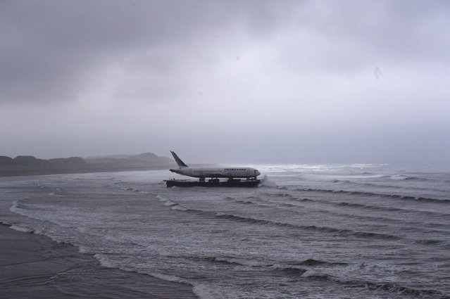IRELAND: Bad weather surrounds a Boeing 767 airplane as it arrives onto Enniscrone beach after it was tugged from Shannon airport out to sea around the west coast of Ireland, May 7, 2016. It is destined for local funeral director David McGowan's proposed Glamping Village to be used as accommodation in Sligo, Ireland. (Photo by Clodagh Kilcoyne/Reuters)