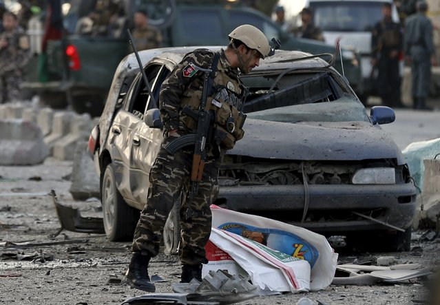 An Afghan security force inspects the site of a suicide attack in Kabul March 25, 2015. (Photo by Omar Sobhani/Reuters)