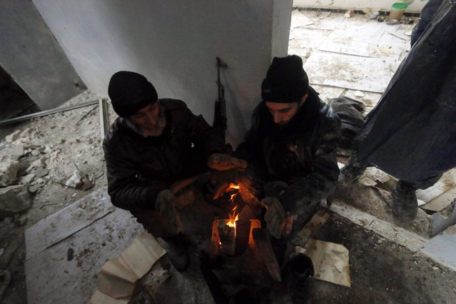 Rebel fighters warm themselves around a fire as they rest at al-Breij frontline, after what they said an advance by them in the area and they took control of 2 factories and several buildings where forces loyal to Syria's President Bashar al-Assad were stationed, in Aleppo January 5, 2015. (Photo by Hosam Katan/Reuters)