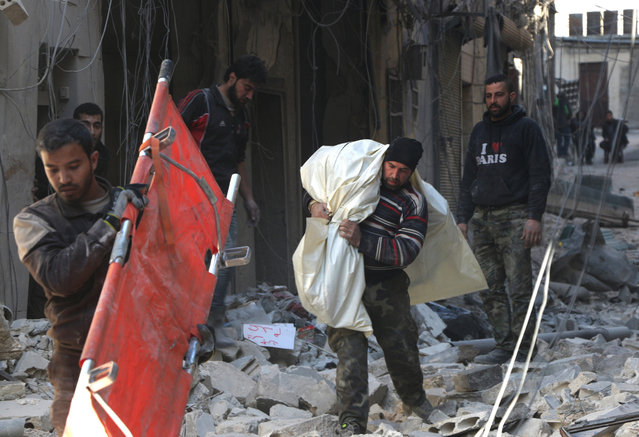 Civil defense team members try to search casualties after the war crafts belonging to the Russian army carried out airstrikes on opposition controlled residential areas at the al Qallasa neighbourhood in Aleppo, Syria on February 4, 2016. (Photo by Beha el Halebi/Anadolu Agency/Getty Images)